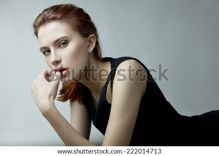 Fashion beauty portrait of young red-haired model with long straight hair in black dress.