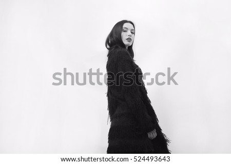 Fashion beauty swag girl wearing black fur coat. Black and white gorgeous young woman portrait. Vogue style on white background in studio. Fashion studio light.
