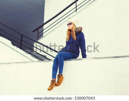 Fashion blonde woman sitting in winter city over white wall background