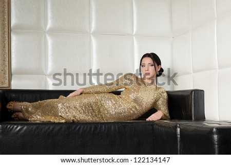 Fashion brunette woman in gold dress on sofa