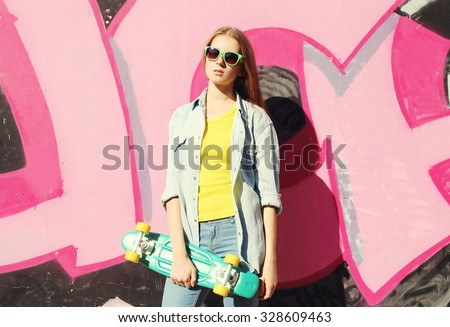 Fashion cool girl wearing a sunglasses, jeans shirt and skateboard in city