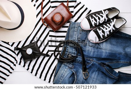 Fashion. Fashionable men's jeans, sweater, gumshoes, watches and wallets on a wooden background
