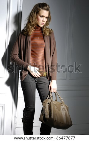 Fashion girl with handbag posing in light background