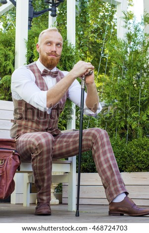 Fashion man with long red beard and resting outdoors