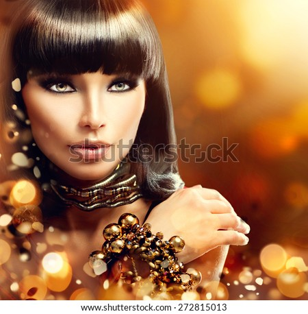 Fashion model brunette girl with golden accessories over gold shiny background. Golden Jewellery. Gold Jewelry. Beauty Egyptian Style Woman with Gold Accessories. Golden bracelet and Necklace