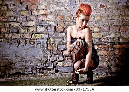 Fashion model in front of a brick wall