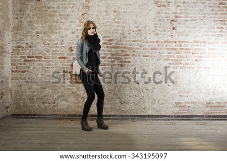 Fashion model wearing leather pants and jacket posing in the old building wall