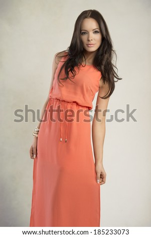 fashion portrait of pretty brunette girl with long orange dress, natural hair-style and bracelets