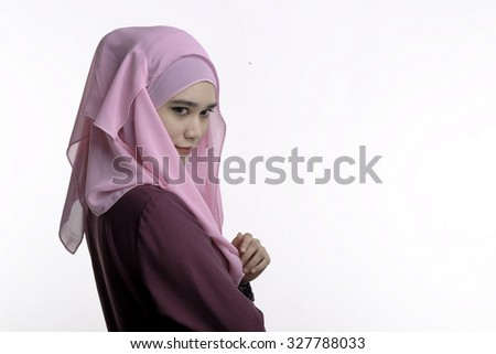 Fashion portrait of young beautiful muslim woman with maroon costume wearing pink color hijab isolated on white background