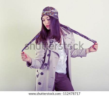 Fashion portrait of young beautiful woman in the raincoat and bandana