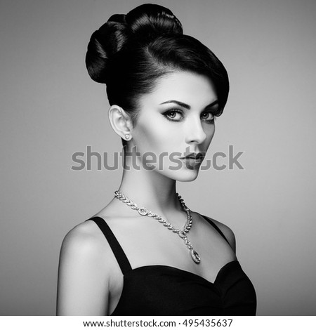 Fashion portrait of young beautiful woman with jewelry and elegant hairstyle. Brunette girl. Perfect make-up.  Beauty style woman with diamond accessories. Black and White