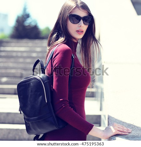 Fashion portrait of young elegant brunette woman outdoor. Cherry dress, leather backpack, sunglasses