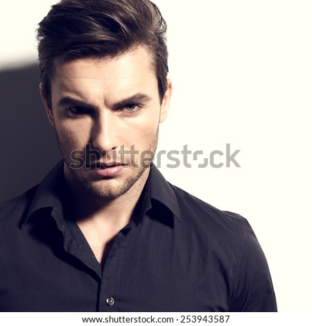 Fashion portrait of young man in black shirt poses over wall with contrast shadows