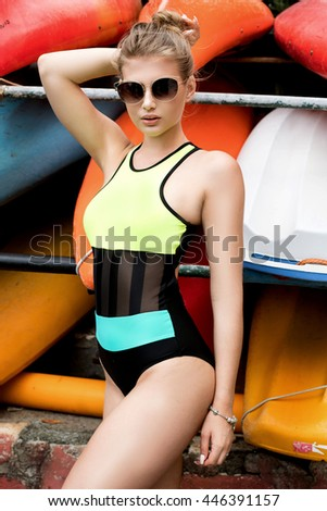 Fashion portrait of young stylish pretty girl in colorful swimsuit. Vacation mood. Summer sunny day.