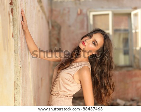 fashion portrait of young woman, in an old house, in ruin, standing next to a brick wall