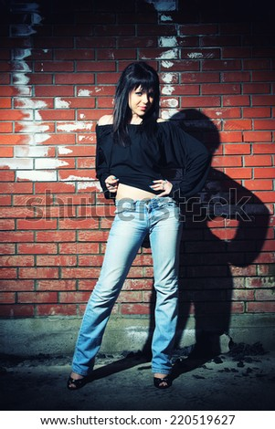 fashion portrait of young woman with a brick wall in the background