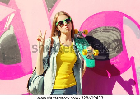 Fashion pretty cool girl wearing a sunglasses and skateboard having fun in city over colorful background