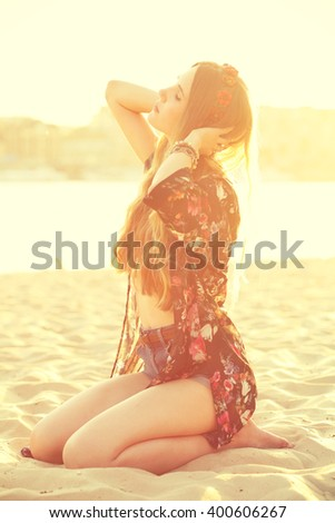 Fashion shot of a beautiful boho style girl over sunlight background. Happy carefree young woman outdoors, bohemian, hippie, oriental