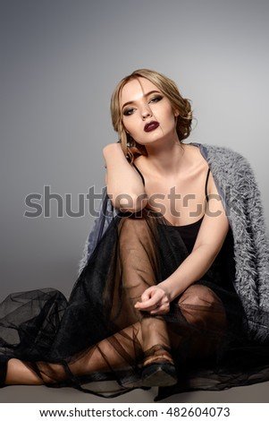 Fashion shot of a beautiful young woman in black evening dress and fur jacket. Studio shot.