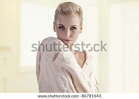 fashion shot of a gorgeous blonde girl with an elegant up-do wearing a warm winter sweater