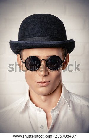 Fashion shot of a modern young man in white shirt, black bowler hat and round sunglasses.