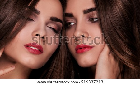 Fashion studio photo of two beautiful young ladies . Beauty portrait of twins sisters. Perfect face makeup.