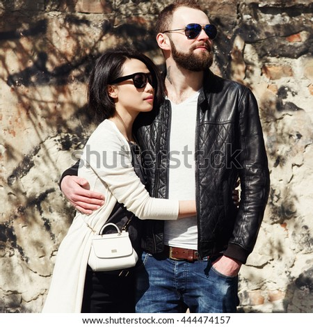 Fashionable couple in sunglasses hugging near old wall