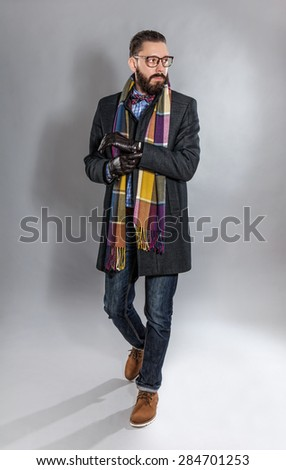 Fashionable handsome stylish bearded man in coat and in a checkered scarf and bow tie.