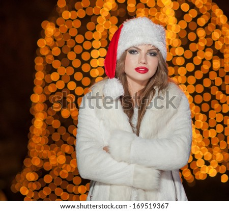 Fashionable lady wearing Xmas hat and white fur coat outdoor. Portrait of young beautiful woman in winter style. Bright picture of beautiful blonde woman with make up wearing Santa hat