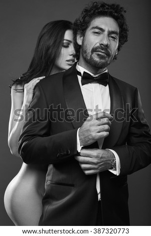 Fashionable portrait of elegant sexy couple in studio. Naked beautiful woman touching a brutal man in suit on dark background. Grayscale
