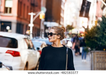 Fashionable woman model walking on New York City street wearing sunglasses and black sweater