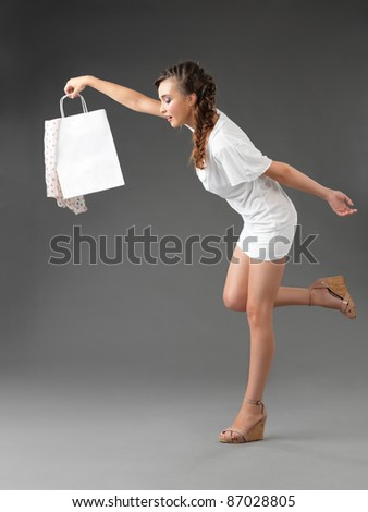 fashionable young woman holding a shoppping bag, tumbling