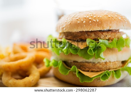 fast food, junk-food and unhealthy eating concept - close up of hamburger or cheeseburger on table