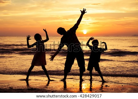 Father and children  playing on the beach at the sunset time. Concept of friendly family.