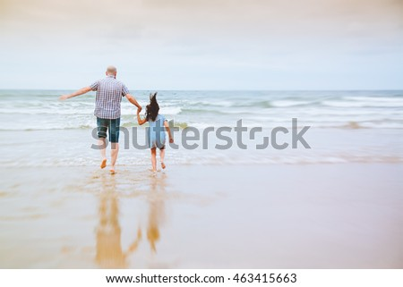 Father and daughter holding hands running to the waves in a cloudy day. Zoom effect.