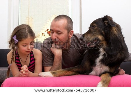 Father and daughter lie with their dog on the couch