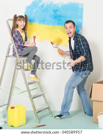 Father and daughter makes repairs at home - painting big Ukrainian flag on wall at home.