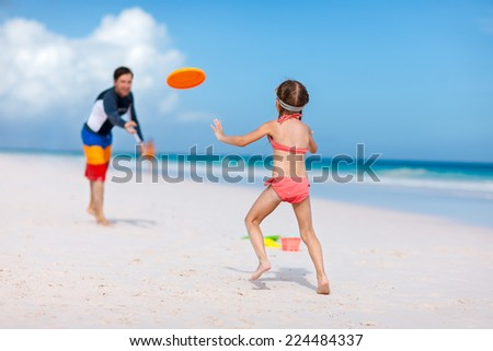 Father and daughter playing with flying disk at beach