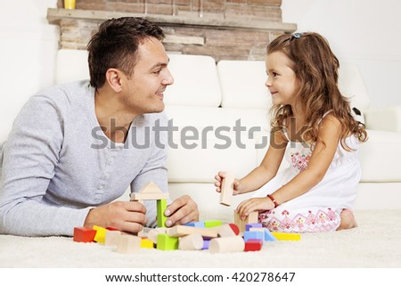 Father and daughter playing with wooden blocks on the floor.