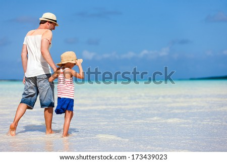Father and daughter walking on a deserted tropical beach