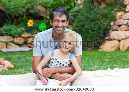 Father and daughter writing together in a park