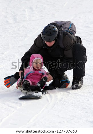 Father and his toddler daughter sliding on snowboard