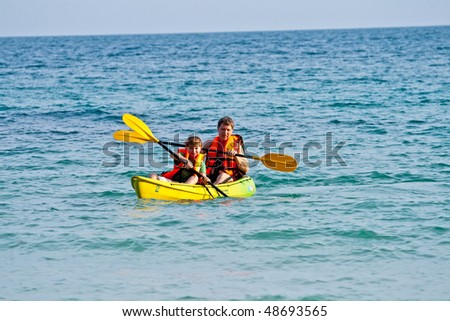 father and son are paddling with a canoe in open sea