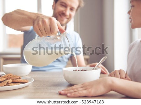 Father and son are smiling while having a breakfast in kitchen. Dad is pouring milk into bowls