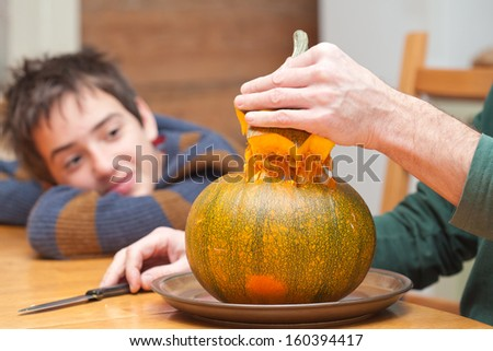 father and son carving Halloween pumpkin on a kitchen table, candid shot