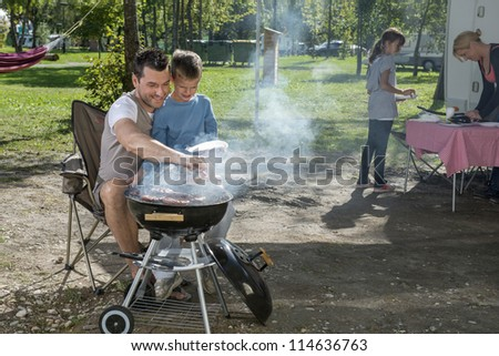 Father and son cooking in front of mobile van