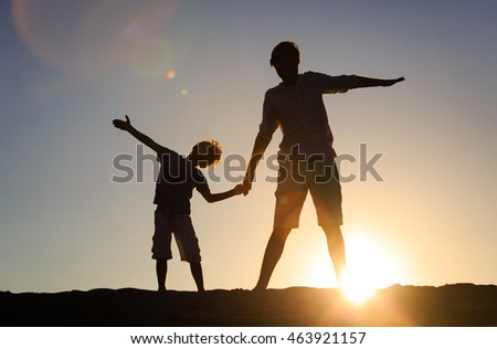father and son having fun on sunset