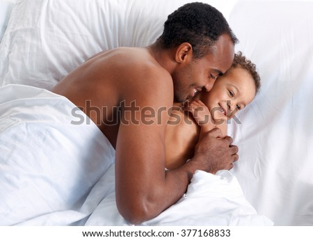 Father and son lie in bed, family relationship. Hispanic man with his son in bed