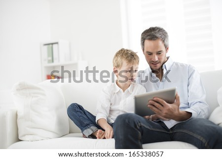 father and son playing on a tablet