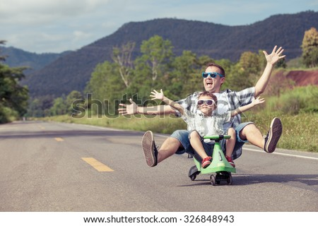 Father and son playing  on the road at the day time.  Concept of friendly family.